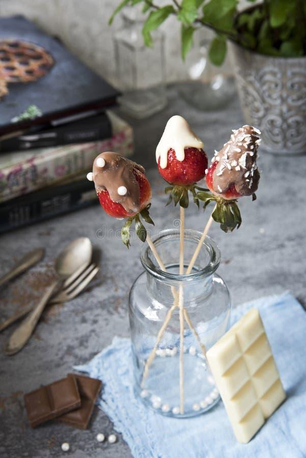 Καλυμμένες σοκολάτα φράουλες σε ένα αναδρομικό υπόβαθρο σε ένα αναδρομικό υπόβαθρο στοκ εικόνες