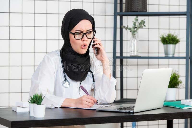 Καλυμμένη η θηλυκό συνεδρίαση επιστημόνων στο γραφείο της που εξετάζει το lap-top ανοίγει το στόμα της με τη συγκλονισμένη συγκίν στοκ φωτογραφίες με δικαίωμα ελεύθερης χρήσης
