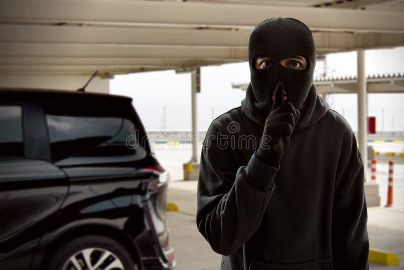 Καλυμμένος κλέφτης που προσπαθεί να κλέψει το αυτοκίνητο στοκ εικόνες