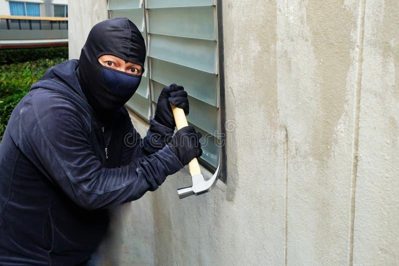 Καλυμμένος κλέφτης που χρησιμοποιεί ένα σφυρί που προσπαθεί να σπάσει τα παράθυρα στοκ φωτογραφίες