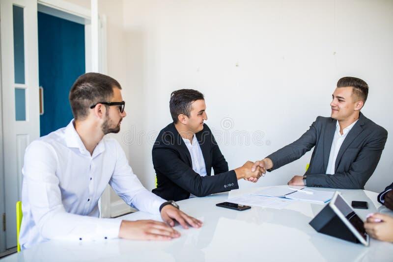 Καλωσορίστε εν πλω Ομάδα βέβαιων επιχειρηματιών στη formalwear συνεδρίαση στον πίνακα μαζί και χαμογελώντας ενώ δύο άτομα στοκ φωτογραφία με δικαίωμα ελεύθερης χρήσης