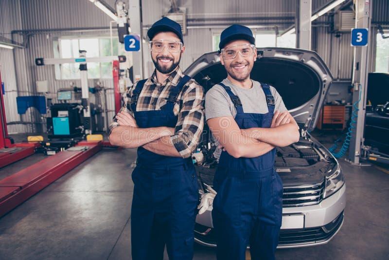 Καλωσορίστε στην υπηρεσία αυτοκινήτων μας Δύο εμπειρογνώμονες με τα όπλα που διασχίζονται, smil στοκ φωτογραφίες