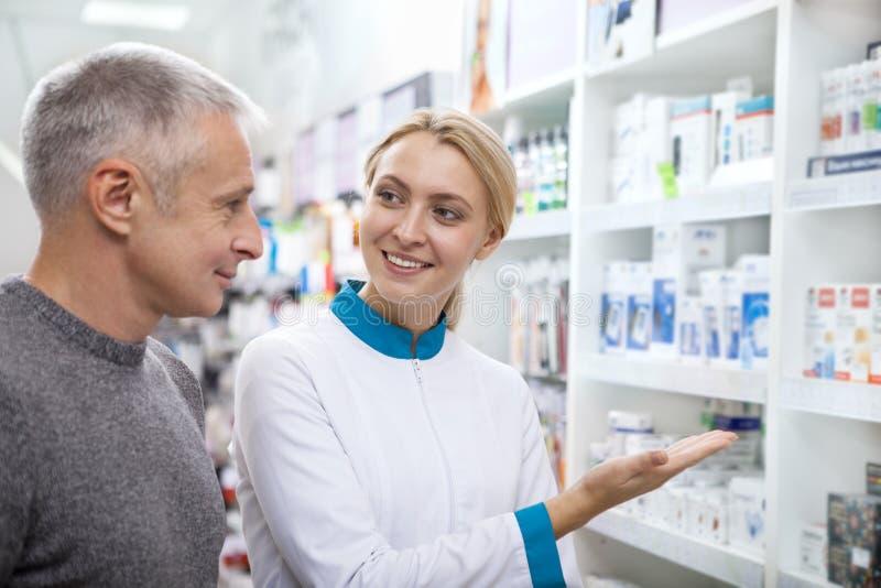 Καλός θηλυκός φαρμακοποιός που βοηθά τον πελάτη της στοκ εικόνες