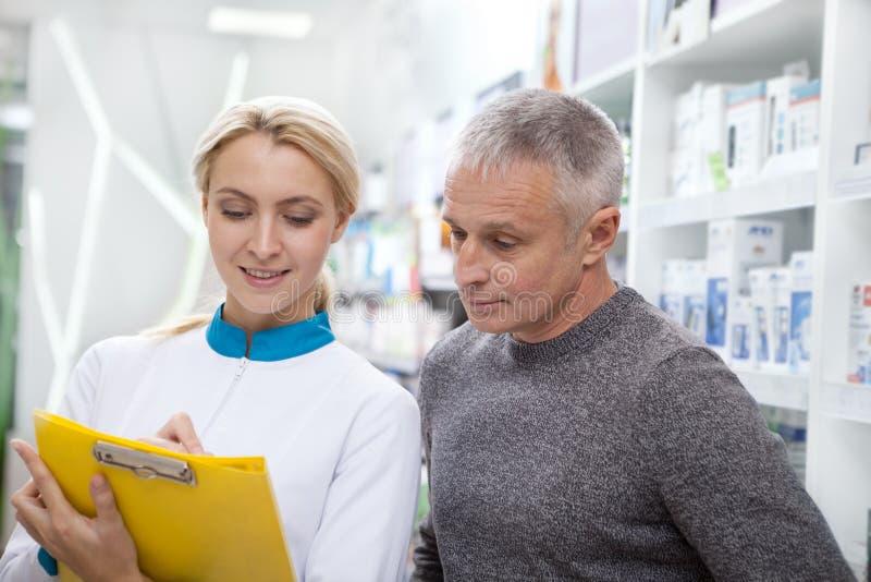 Καλός θηλυκός φαρμακοποιός που βοηθά τον πελάτη της στοκ εικόνα