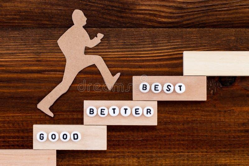 Καλός - καλύτερα - καλύτερος, άτομο εγγράφου που αναρριχείται στα βήματα στην επιτυχία σε μια εννοιολογική εικόνα πέρα από το ξύλ στοκ εικόνες