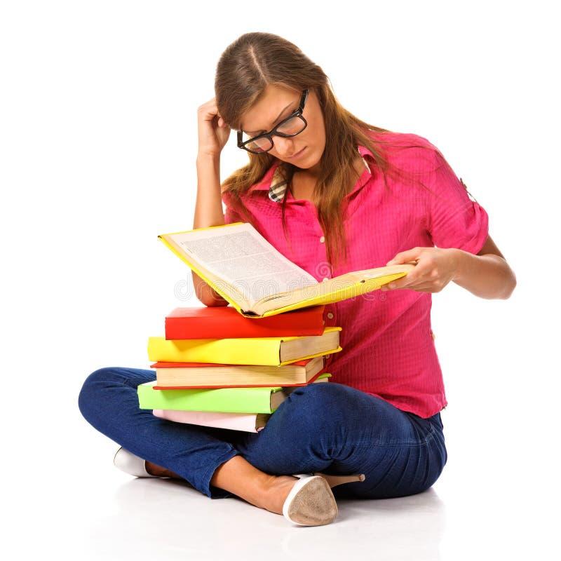 Καλός σπουδαστής με μια στοίβα των βιβλίων, που απομονώνεται στοκ εικόνα