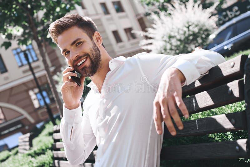Καλός χρόνος εξόδων στην πόλη του Βέβαιος νεαρός άνδρας που κρατά το κινητό τηλέφωνο καθμένος υπαίθρια στοκ εικόνες