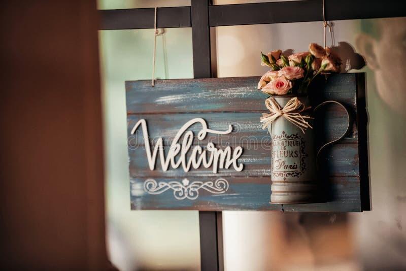Καλό ευπρόσδεκτο σημάδι με την κούπα λουλουδιών στοκ εικόνα με δικαίωμα ελεύθερης χρήσης
