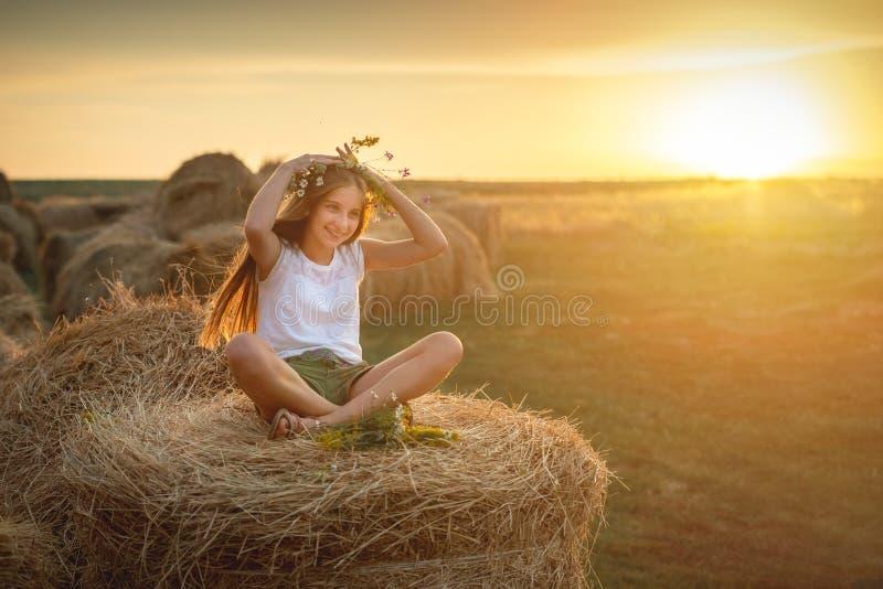 Καλό κορίτσι εφήβων με τη floral ανθοδέσμη, στη θυμωνιά χόρτου στοκ φωτογραφίες