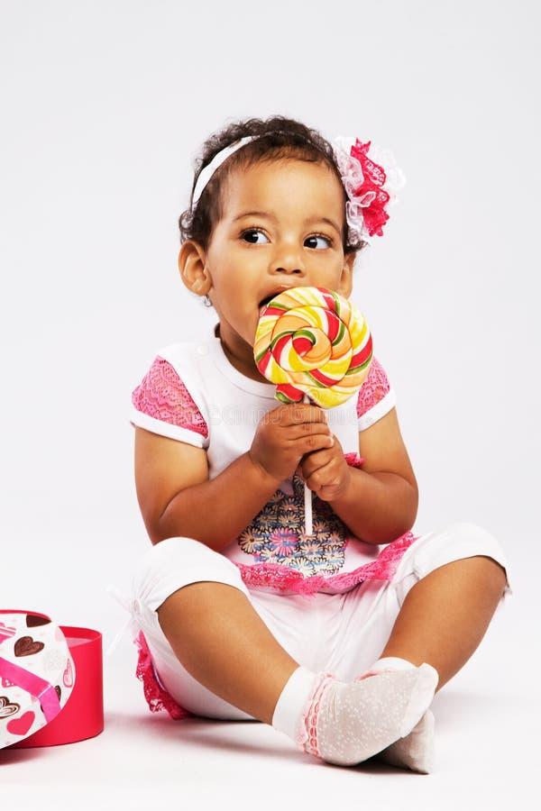 Καλό μικρό κορίτσι που τρώει ένα μεγάλο lollipop στοκ φωτογραφία με δικαίωμα ελεύθερης χρήσης