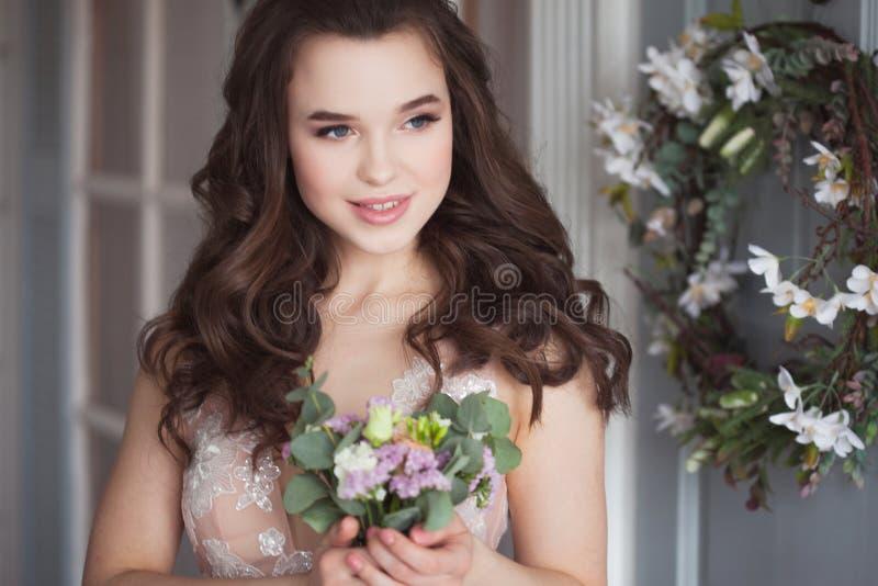 Καλό νέο brunette ν γυναικών ένα δαντελλωτός ρόδινο φόρεμα Ελκυστική νύφη με μια ανθοδέσμη των λουλουδιών στοκ εικόνα