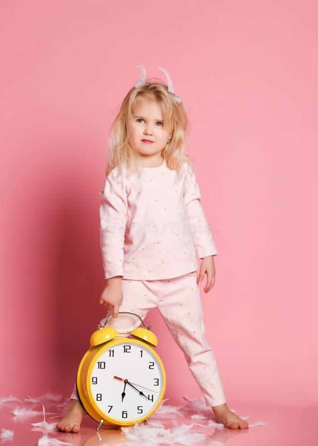 Καλό ξανθό παιχνίδι μικρών παιδιών με το ξυπνητήρι στοκ φωτογραφία