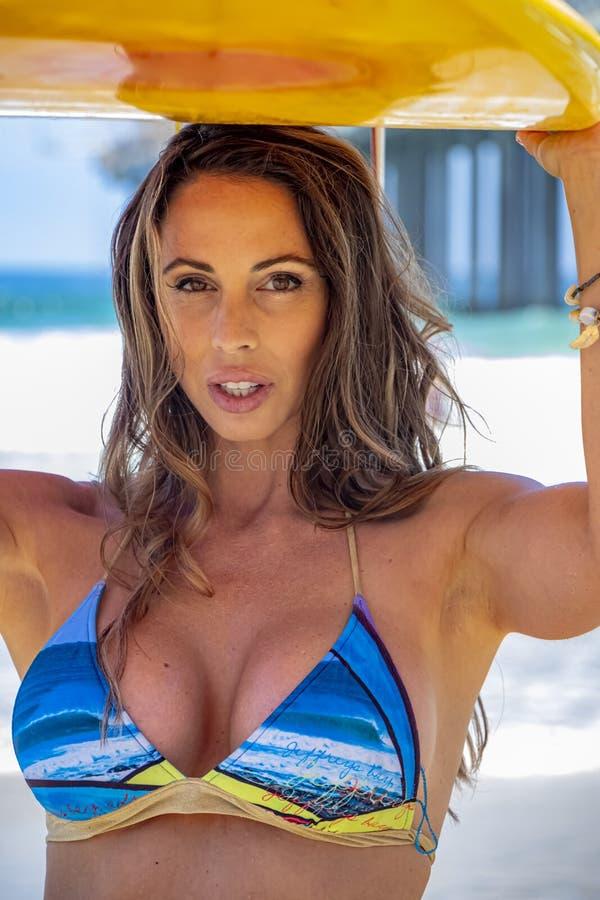 Καλό πρότυπο μπικινιών Brunette με την ιστιοσανίδα της σε μια παραλία στοκ φωτογραφίες