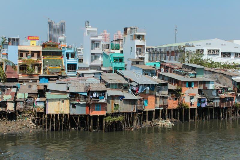 Καλύβες φτωχών γειτονιών στα ξυλοπόδαρα στην όχθη ποταμού στο Ho Chi Minh στοκ εικόνα