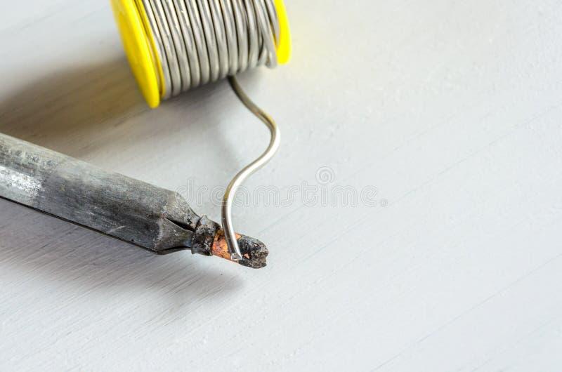 Καλώδιο ύλης συγκολλήσεως και συγκολλώντας σίδηρος με την ξύλινη λαβή στο γκρίζο υπόβαθρο στοκ φωτογραφίες