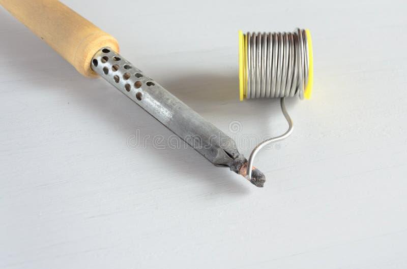 Καλώδιο ύλης συγκολλήσεως και συγκολλώντας σίδηρος με την ξύλινη λαβή στο γκρίζο υπόβαθρο στοκ εικόνες