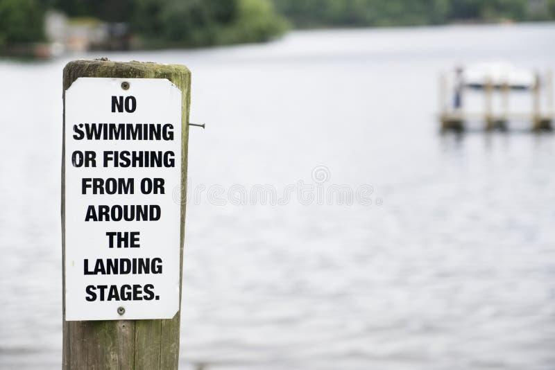Καμία κολύμβηση ή αλιεία στη θέση σημαδιών λιμνών στην ξύλινη αποβάθρα λιμενοβραχιόνων στοκ εικόνα με δικαίωμα ελεύθερης χρήσης