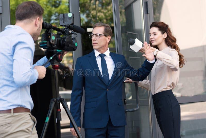 καμεραμάν και anchorwoman με τον επιθετικό επιχειρηματία στοκ εικόνες