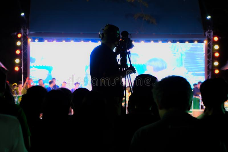 Καμεραμάν στην εργασία, σκιαγραφία του χειριστή καμεραμάν που πυροβολεί ένα τις ζωντανές αποδόσεις Pong Lang στη Μπανγκόκ, Ταϊλάν στοκ εικόνες