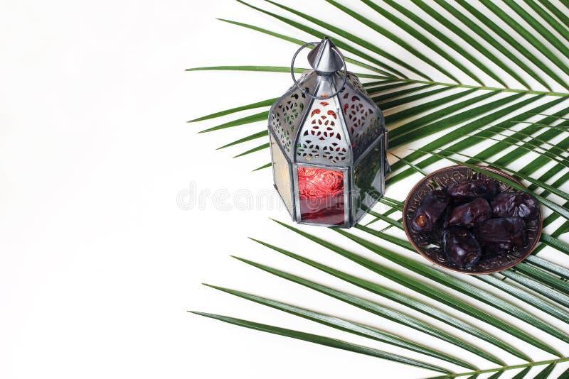 Καμμένος αραβικό φανάρι, πιάτο με τα φρούτα ημερομηνιών και πράσινα φύλλα φοινικών που απομονώνονται στο άσπρο επιτραπέζιο υπόβαθ στοκ φωτογραφία με δικαίωμα ελεύθερης χρήσης
