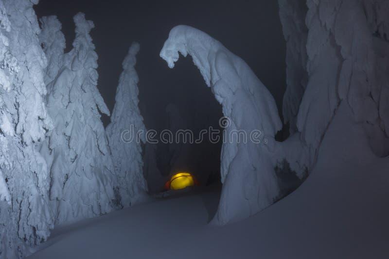 Καμμένος σκηνή στρατοπέδευσης στα βουνά χιονιού στο χειμερινό δάσος σε ένα παραμύθι Ταξίδι μέσω των χειμερινών αλπικών δασών στοκ εικόνα με δικαίωμα ελεύθερης χρήσης