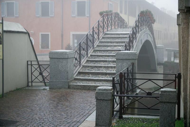 Κανάλι και μια για τους πεζούς γέφυρα, ομιχλώδης καιρός στην Ιταλία στοκ εικόνα