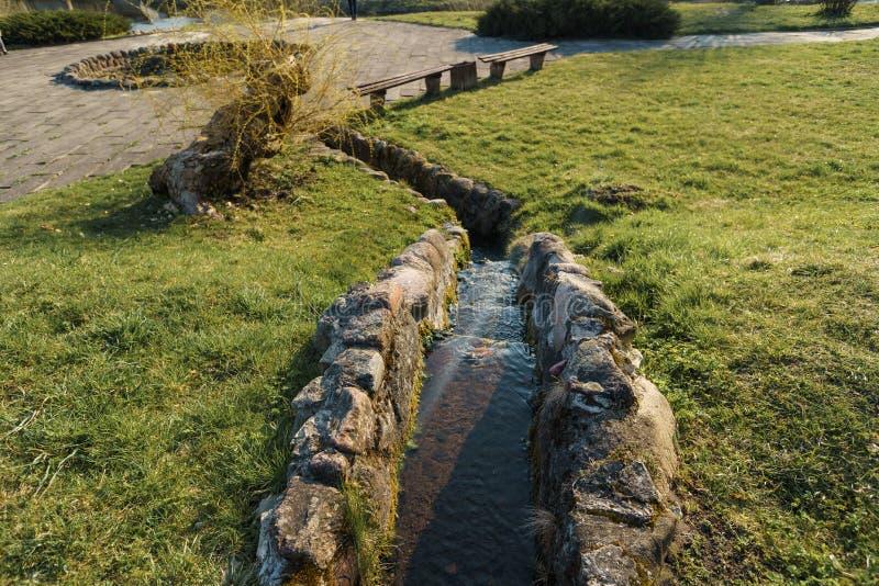 Κανάλι με τα νερά πηγής στην πόλη Sabile στη Λετονία στοκ εικόνες