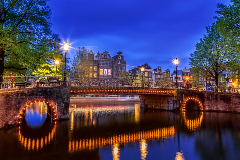 Κανάλι του Άμστερνταμ με τα χαρακτηριστικά ολλανδικά σπίτια και φωτισμένη γέφυρα κατά τη διάρκεια της μπλε ώρας λυκόφατος στην Ολ στοκ φωτογραφία