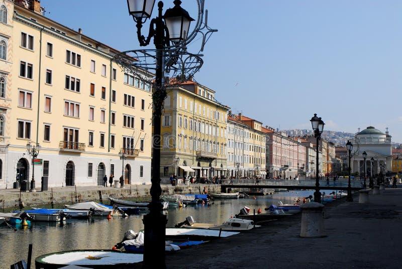 Κανάλι με τις βάρκες, lampposts και τα κτήρια κάτω από το μπλε ουρανό στην Τεργέστη σε Friuli Venezia Giulia (Ιταλία) στοκ εικόνες