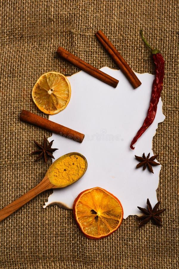 Κανέλα, ξηρά πορτοκάλι και πιπέρι, γλυκάνισο αστεριών γύρω από το κενό έγγραφο για τη συνταγή, διάστημα αντιγράφων Το κουτάλι με  στοκ φωτογραφία με δικαίωμα ελεύθερης χρήσης