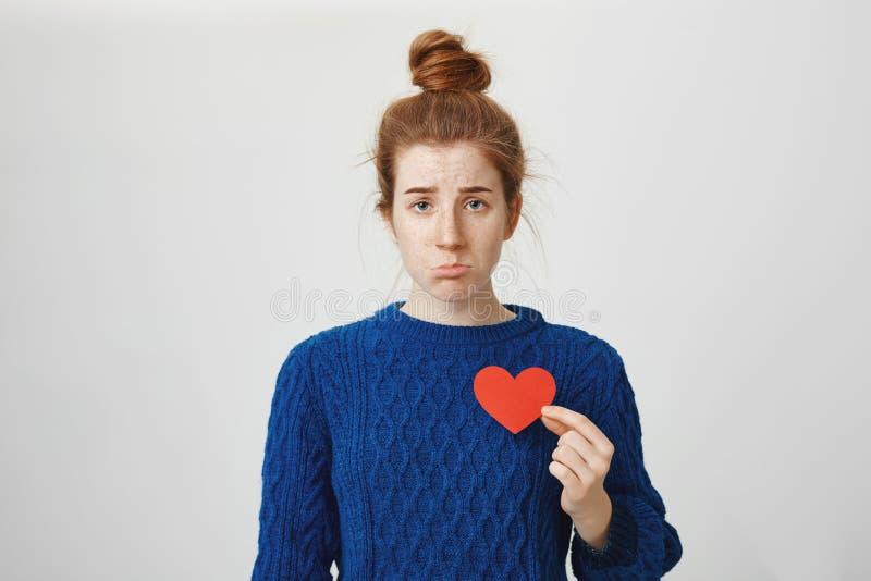 Κανένας δεν με αγαπά Πορτρέτο της χαριτωμένης redhead Ευρωπαίας γυναίκας με την καρδιά εγγράφου εκμετάλλευσης κουλουριών κοντά στ στοκ εικόνα με δικαίωμα ελεύθερης χρήσης