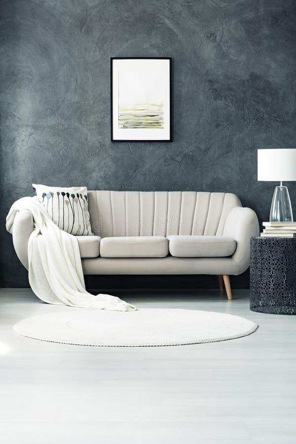 Καναπές από το σκοτεινό γκρίζο τοίχο στοκ εικόνα με δικαίωμα ελεύθερης χρήσης