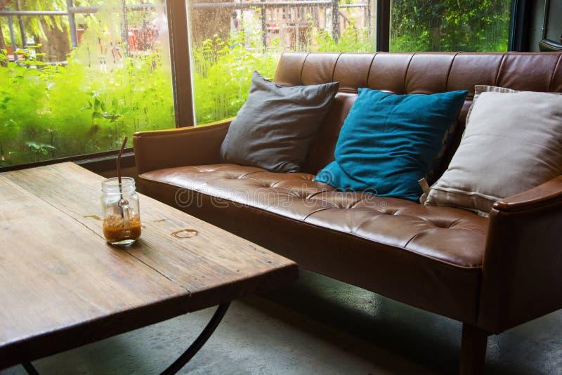 Καναπές δέρματος με ένα ποτήρι του νερού σε έναν ξύλινο πίνακα σε έναν καφέ στοκ φωτογραφία