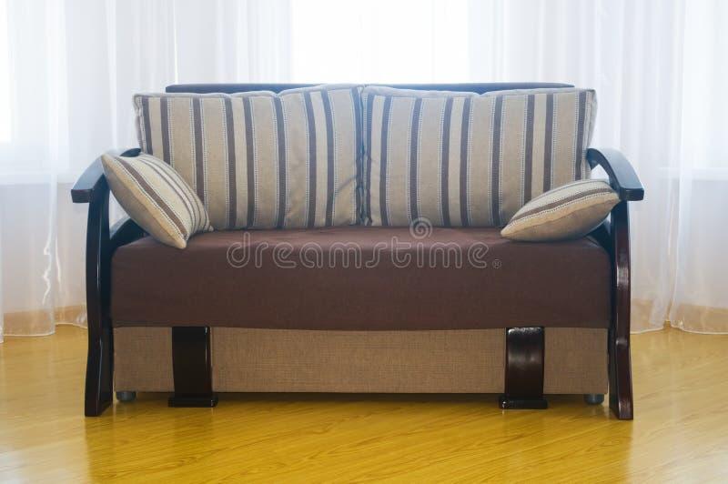 Καναπές κρέμας σχεδιασμένο στο πολυτέλεια δωμάτιο καθίσματος στοκ εικόνα με δικαίωμα ελεύθερης χρήσης