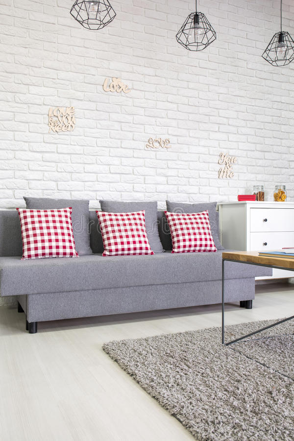 Καναπές με τα κόκκινα μαξιλάρια στοκ εικόνες