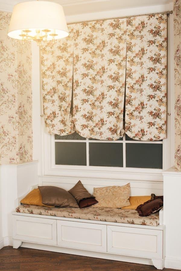 Καναπές με τα μαξιλάρια μπροστά από το παράθυρο και την κουρτίνα στοκ εικόνες με δικαίωμα ελεύθερης χρήσης