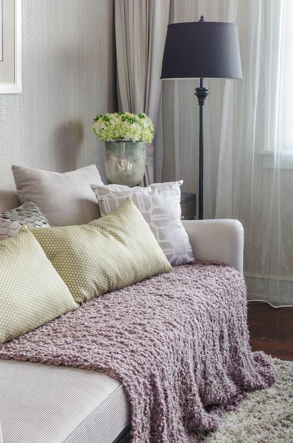 Καναπές πολυτέλειας με τα μαξιλάρια και μαύρος λαμπτήρας στο καθιστικό στοκ εικόνες