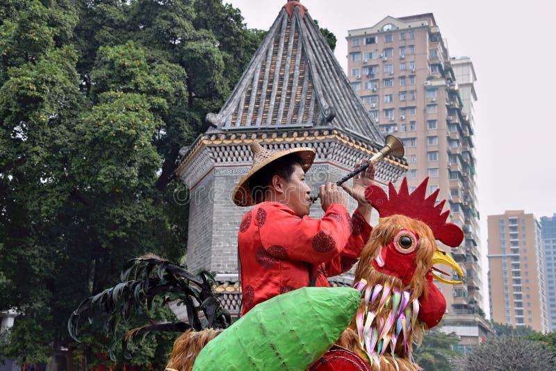 ΚΑΝΤΟΝΙΟ, το Δεκέμβριο του 2017 της ΚΙΝΑΣ â€ «CIRCA: Ο πλανόδιος πωλητής σε Guangzhou ντύνει επάνω ως ζωηρόχρωμος κόκκορας που φυ στοκ εικόνες