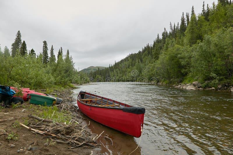 Κανό και εξοπλισμός Beached στον ποταμό στην Αλάσκα στοκ φωτογραφίες