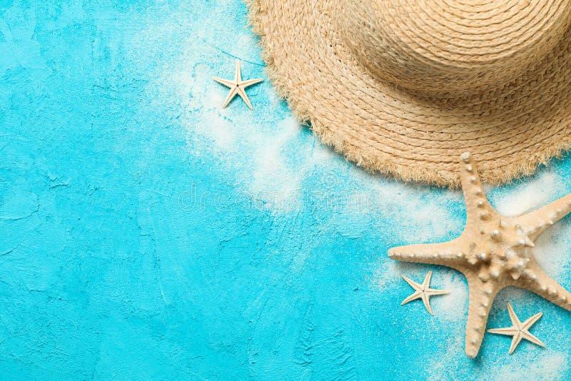 Καπέλο αχύρου, άμμος και αστερίας στο υπόβαθρο χρώματος, διάστημα για το κείμενο r στοκ φωτογραφία με δικαίωμα ελεύθερης χρήσης