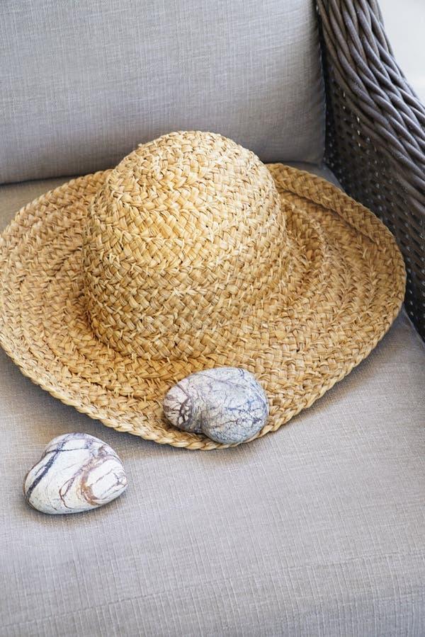 Καπέλο αχύρου με διαμορφωμένους τους καρδιά βράχους στην καρέκλα στοκ φωτογραφία με δικαίωμα ελεύθερης χρήσης