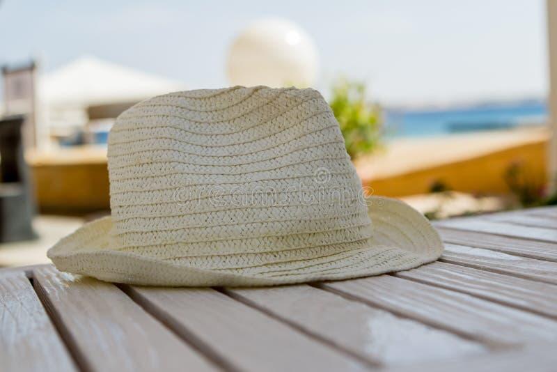 Καπέλο αχύρου σε έναν άσπρο ξύλινο πίνακα στοκ εικόνες