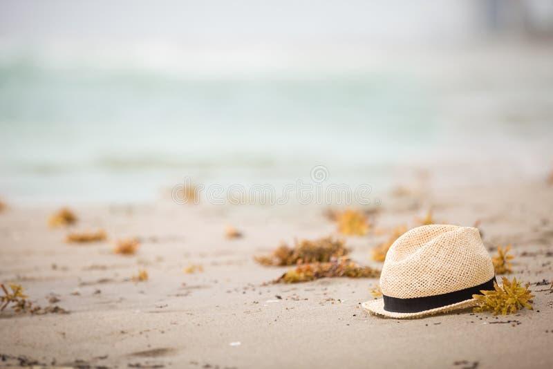 Καπέλο αχύρου της Νίκαιας που βάζει στην άμμο Όμορφο ωκεάνιο υπόβαθρο παραλιών r Χρόνος διακοπών Τέλος των θερινών διακοπών στοκ φωτογραφία με δικαίωμα ελεύθερης χρήσης