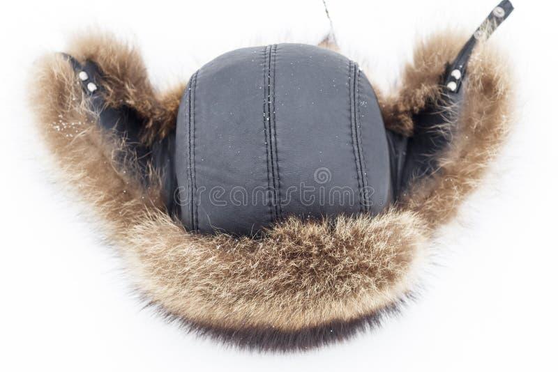 Καπέλο γουνών για το χειμώνα για τα άτομα, στο φυσικό χιόνι υπάρχει τονισμός και κινηματογράφηση σε πρώτο πλάνο στοκ εικόνες με δικαίωμα ελεύθερης χρήσης