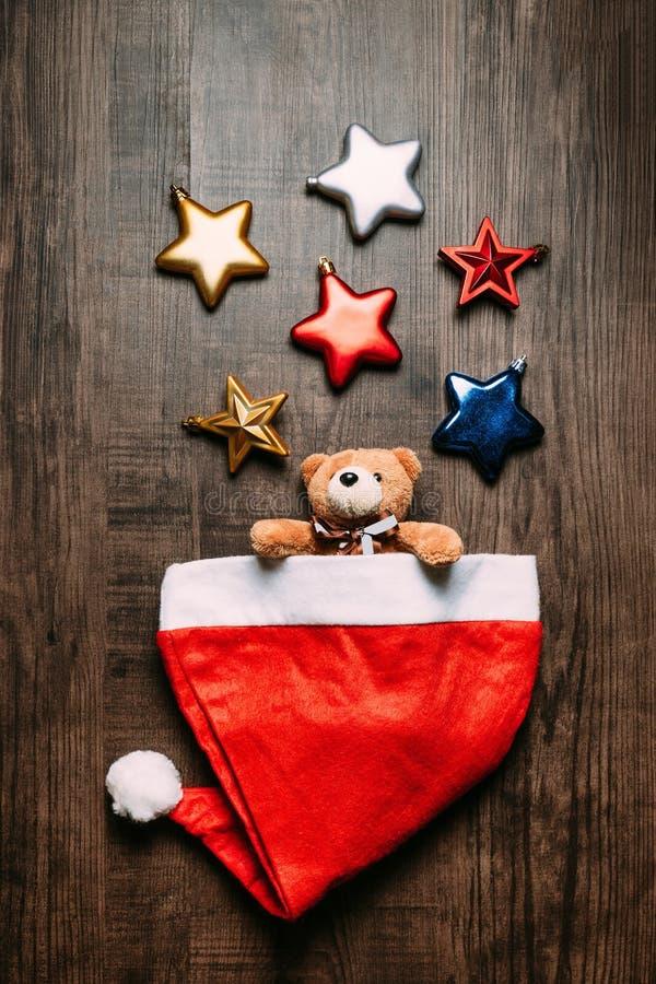 Καπέλο Santa με τα teddy εσωτερικά και μεταλλικά αστέρια αρκούδων στο ξύλινο υπόβαθρο Επίπεδος βάλτε για τα Χριστούγεννα και το έ στοκ φωτογραφίες