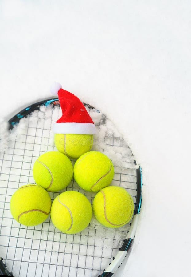 Καπέλο Santa στη σφαίρα αντισφαίρισης, σύνολο σφαιρών αντισφαίρισης στο δέντρο έλατου μορφής στη ρακέτα στο άσπρο χειμερινό υπόβα στοκ φωτογραφίες με δικαίωμα ελεύθερης χρήσης
