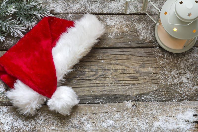 Καπέλο Άγιου Βασίλη στο εκλεκτής ποιότητας ξύλινο υπόβαθρο Χριστουγέννων πινάκων στοκ εικόνα
