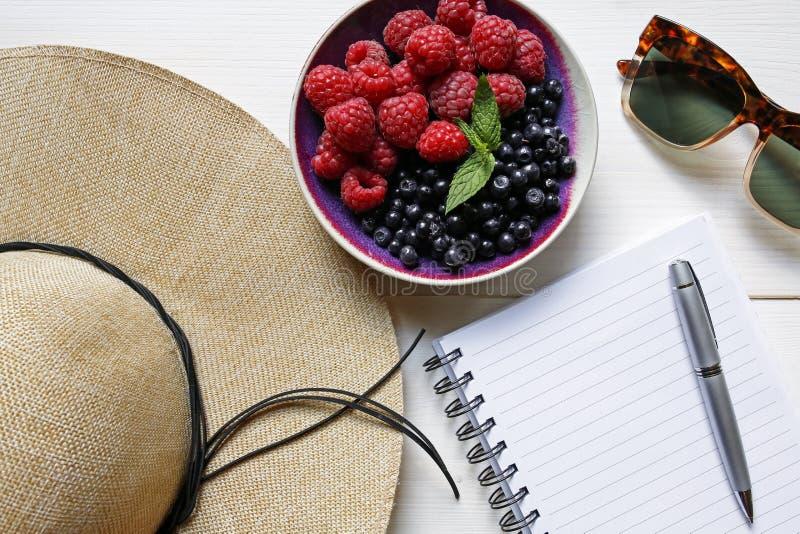 Καπέλο αχύρου θερινής πλανίζοντας έννοιας, φρούτα, γυαλιά ηλίου και σημειωματάριο στοκ φωτογραφία