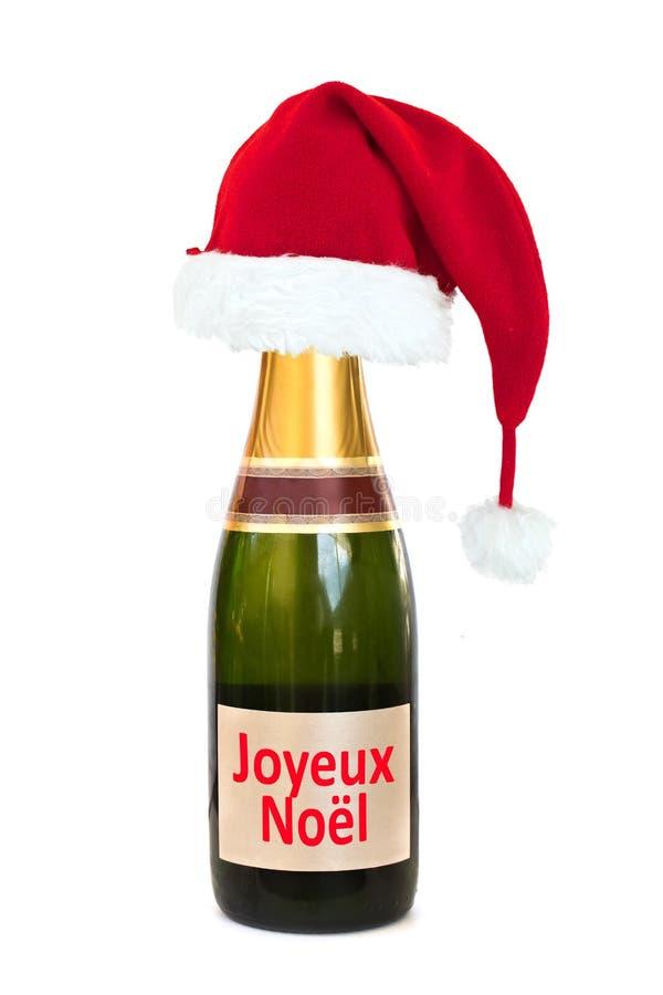 Καπέλο Χριστουγέννων σε ένα μπουκάλι Joyeux Noel CHAMPAGNE (Χαρούμενα Χριστούγεννα), που απομονώνεται στο λευκό στοκ φωτογραφία με δικαίωμα ελεύθερης χρήσης