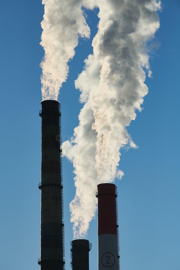Καπνίζοντας σωλήνες ή καπνοδόχοι των εγκαταστάσεων παραγωγής ενέργειας ή electropower του σταθμού μπλε ρύπανση εργοστασίων ανασκό στοκ εικόνα με δικαίωμα ελεύθερης χρήσης